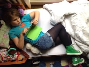 A photograph of a girl lying diagonally across a bed.