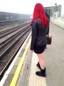 A woman in black standing on a train platform.