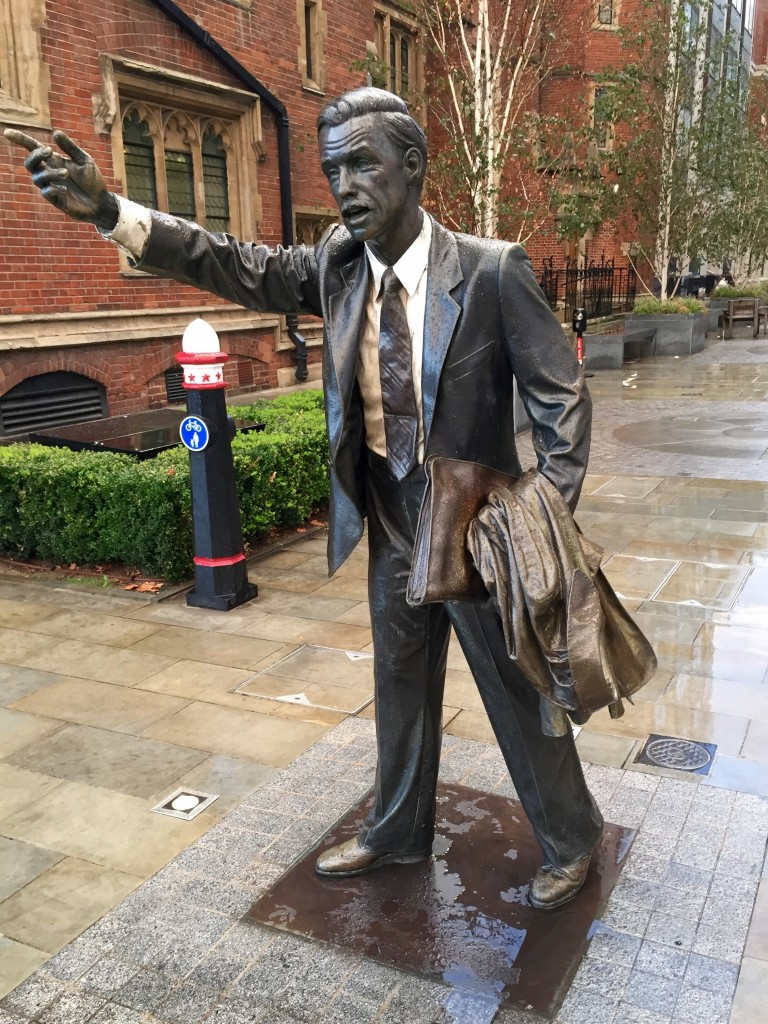 A life-size bronze sculpture of a business man hailing a taxi.